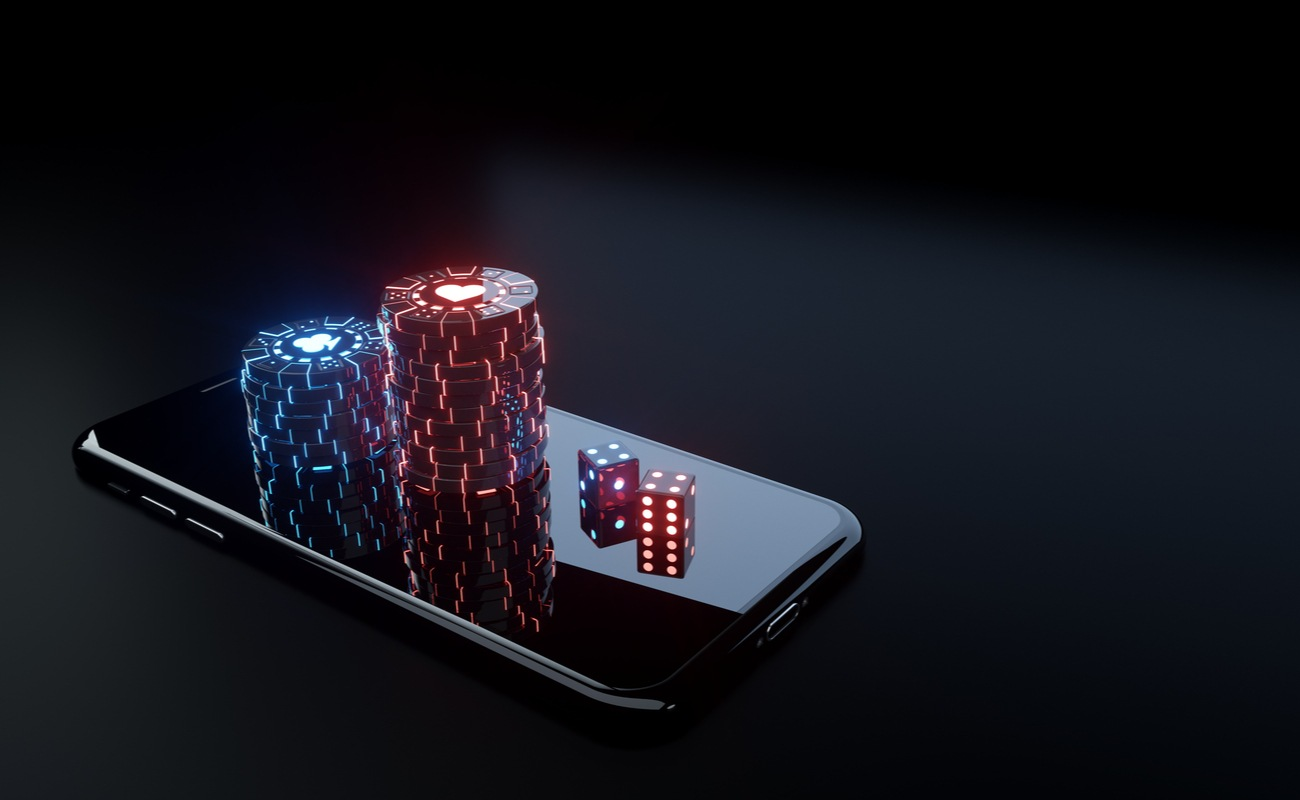Neon poker chips and dice on top of a mobile phone