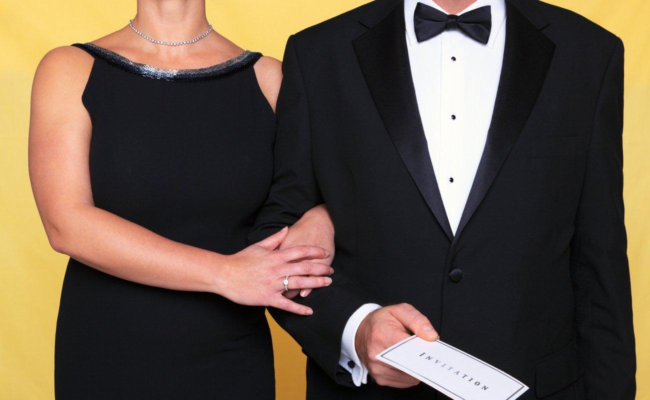 Pria dan wanita berpakaian untuk acara dasi hitam