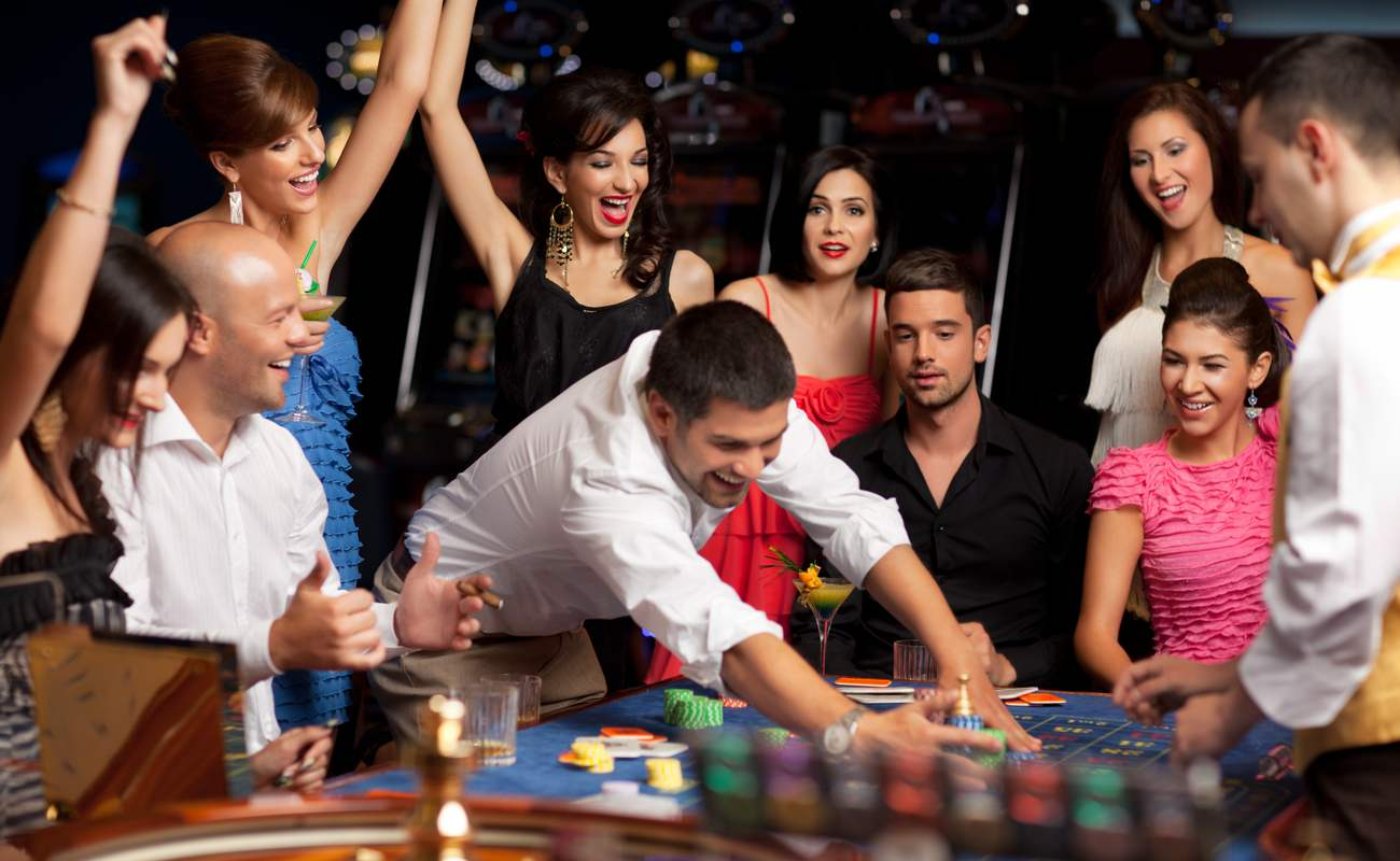 Group of people enjoying themselves at a casino playing Roulette