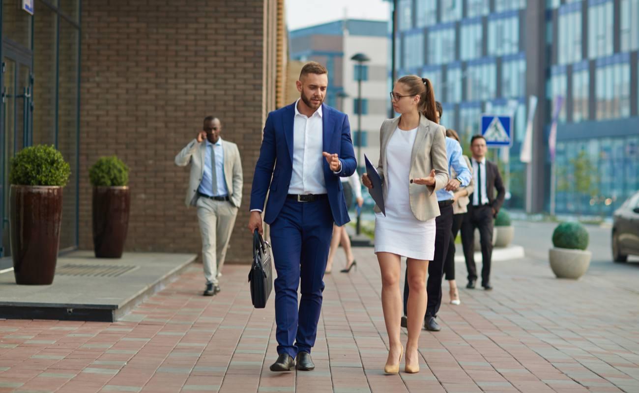 Pria dan wanita berjalan dalam pakaian formal bisnis
