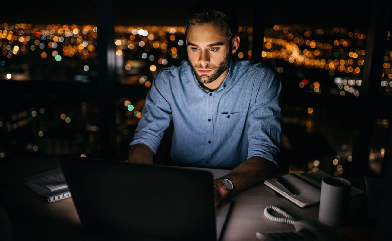 Man looking at his laptop screen in the dark