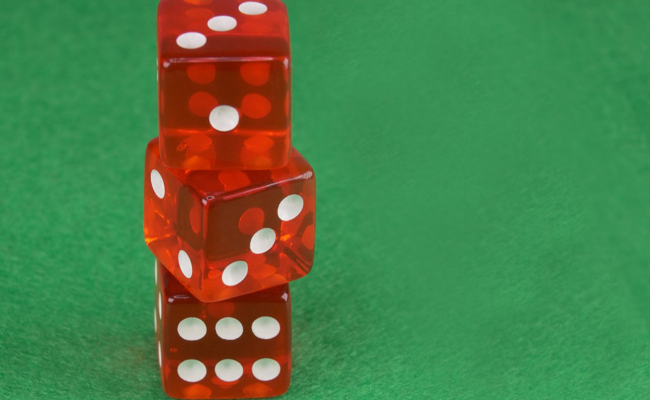 Three red dices on green cloth