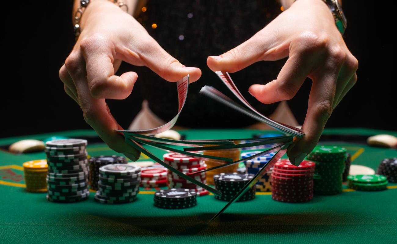 bandar mengocok kartu poker di kasino di depan chip di atas meja