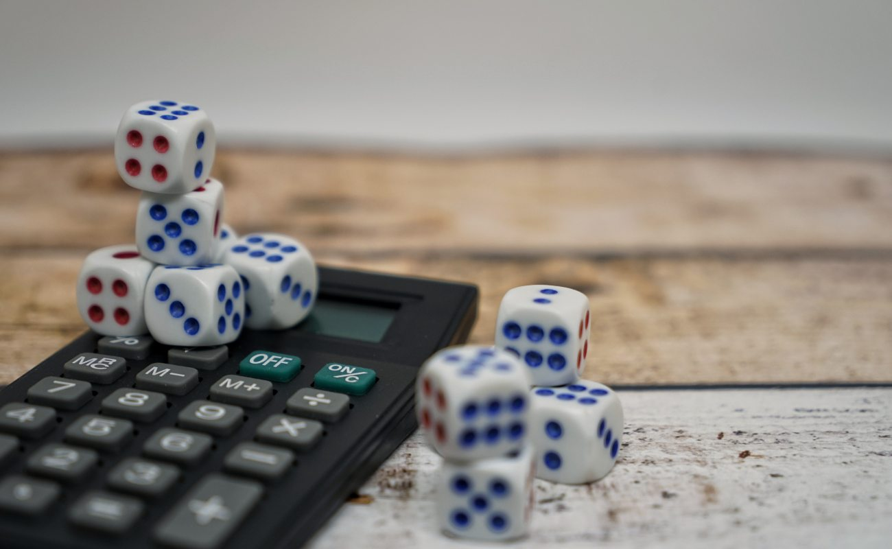 Dice placed on and next to a calculator on a wooden background.