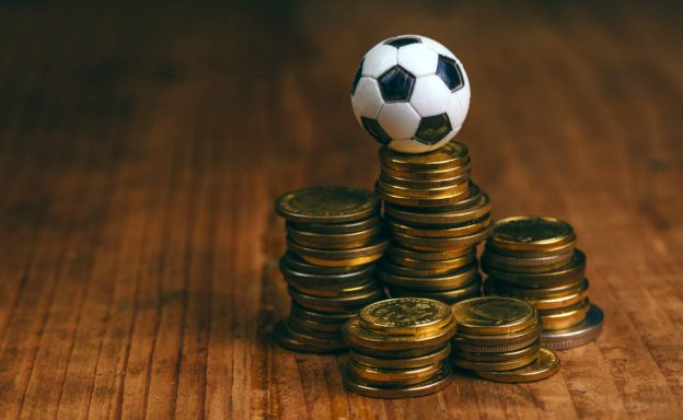 Stacks of coins with a football ball on the top of one of them.