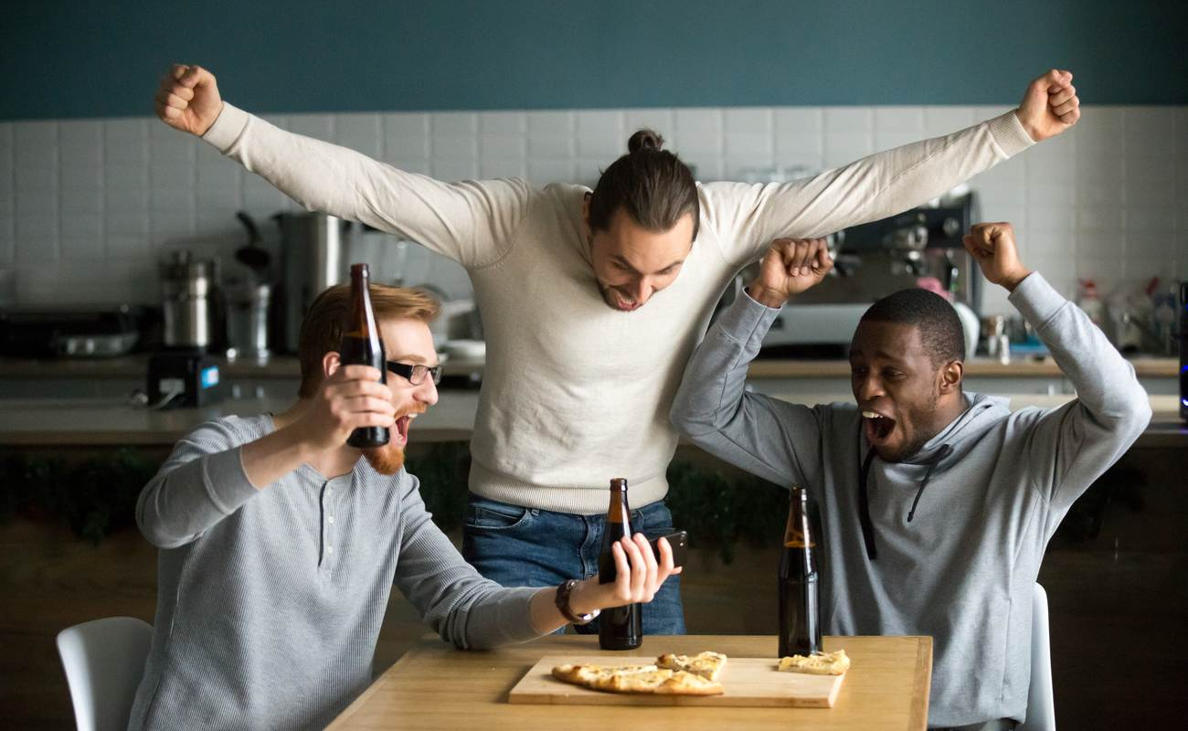 3 friends celebrating winning a sports bet looking at a phone