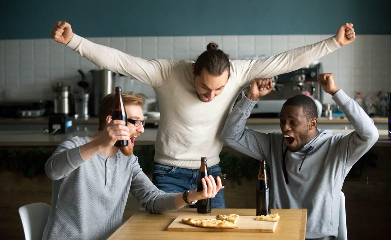 3 teman merayakan kemenangan taruhan olahraga sambil melihat telepon