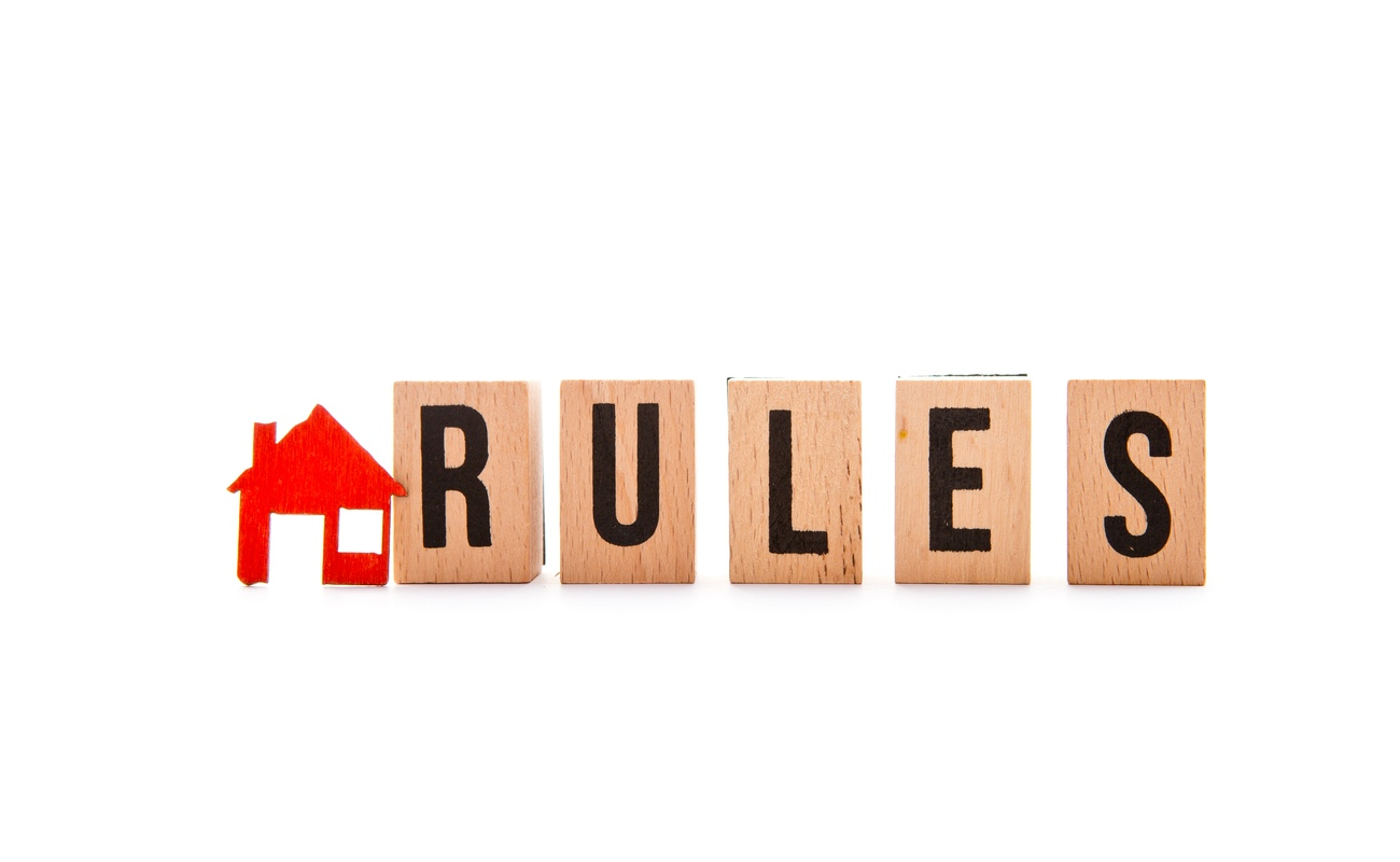 House rules concept with a red house and rules spelt out with wooden blocks