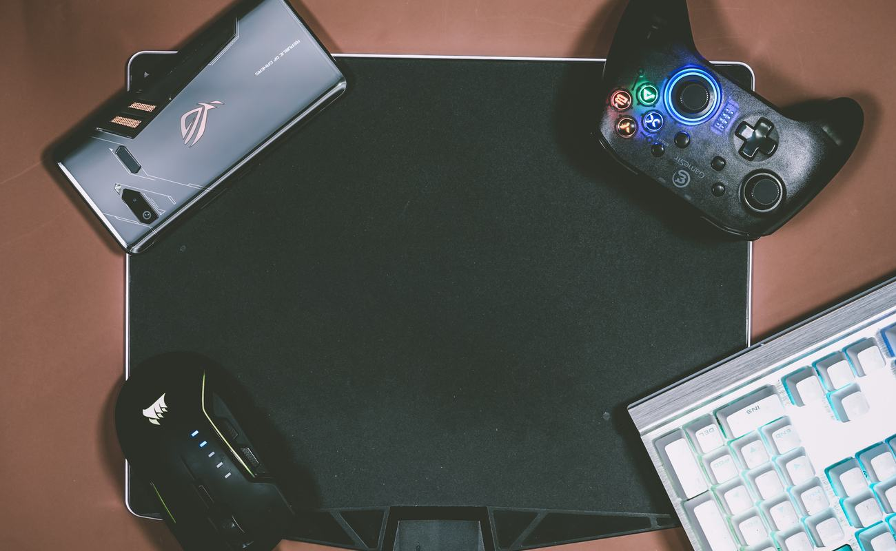 Keyboard, mouse, phone and controller placed on each corner of a mousepad