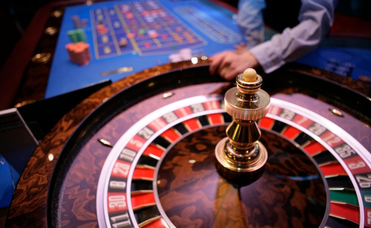 Meja roulette dengan dealer di latar belakang