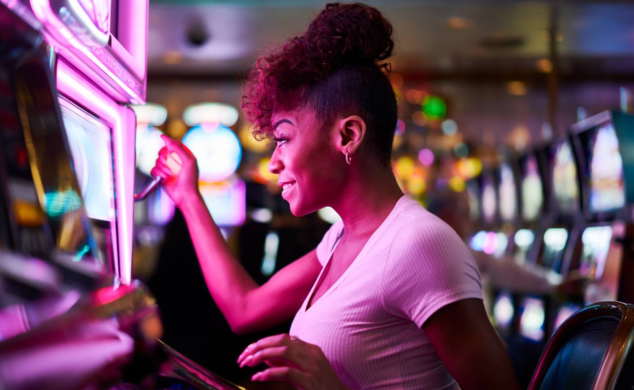 Woman enjoying playing a slot machine with her hand on the lever