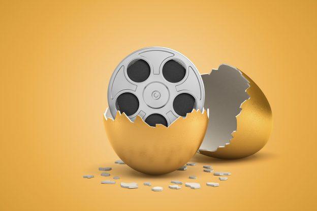 3d rendering of broken in two golden egg with retro film reel inside on light ocher background. - stock photo