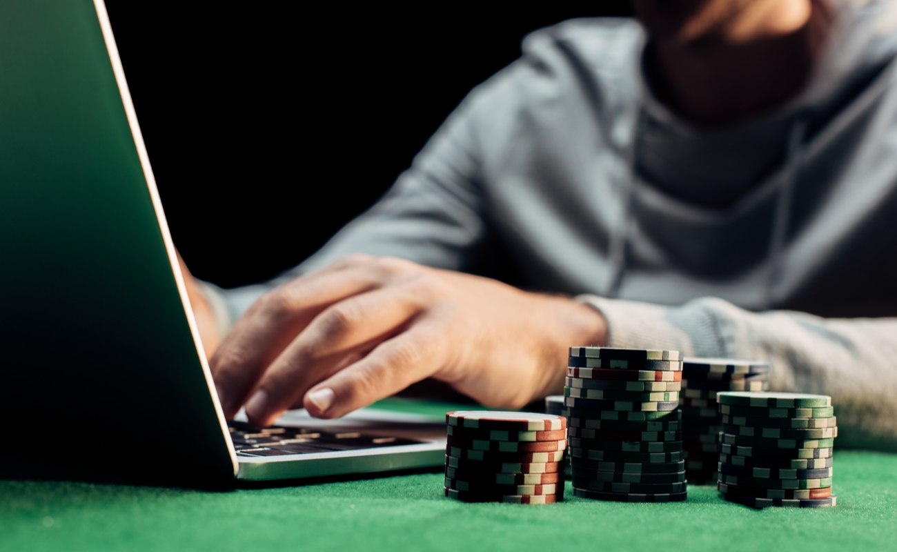 Person using a laptop with multiple stacks of poker chips next to the laptop