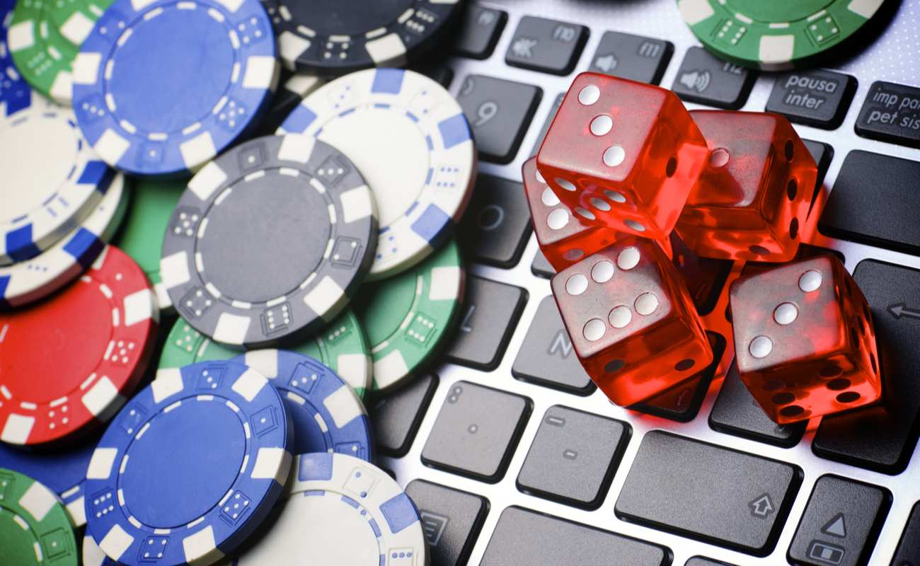 Lots of poker chips and dice on top of a laptop keyboard