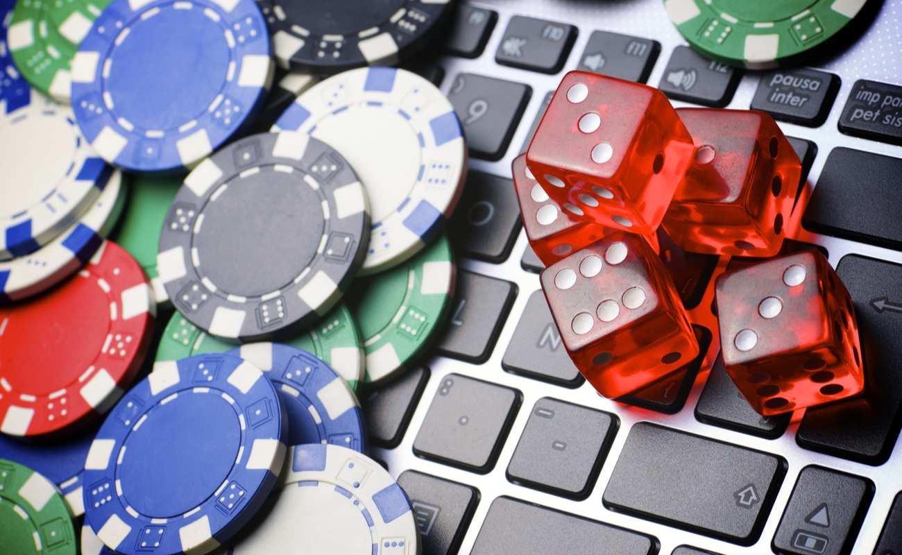 Banyak chip poker dan dadu di atas keyboard laptop