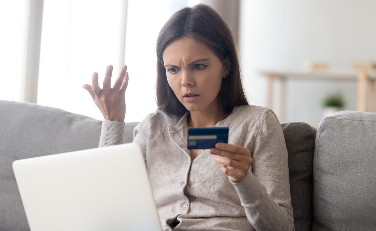 seorang wanita yang memegang kartu kredit dan menatap laptopnya dengan tidak percaya